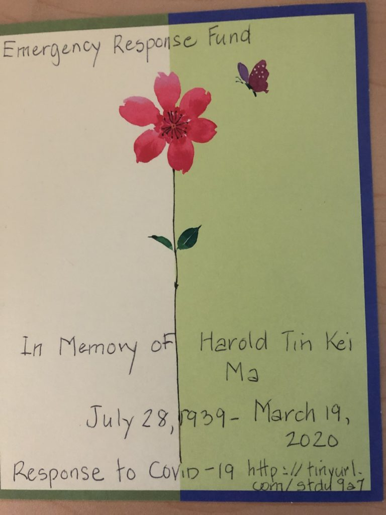 "A photograph of a card with a flower and butterfly on it, and in hand writing it reads ""Emergency Response Fund. In memory of Harold Tin Kei Ma. July 28, 1939 - March 19, 2020. Response to COVID-19 http://tinyurl.com/stdu9a7"""